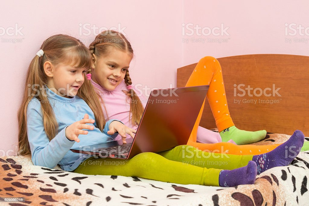 Two girls sitting on the bed with laptop stock photo