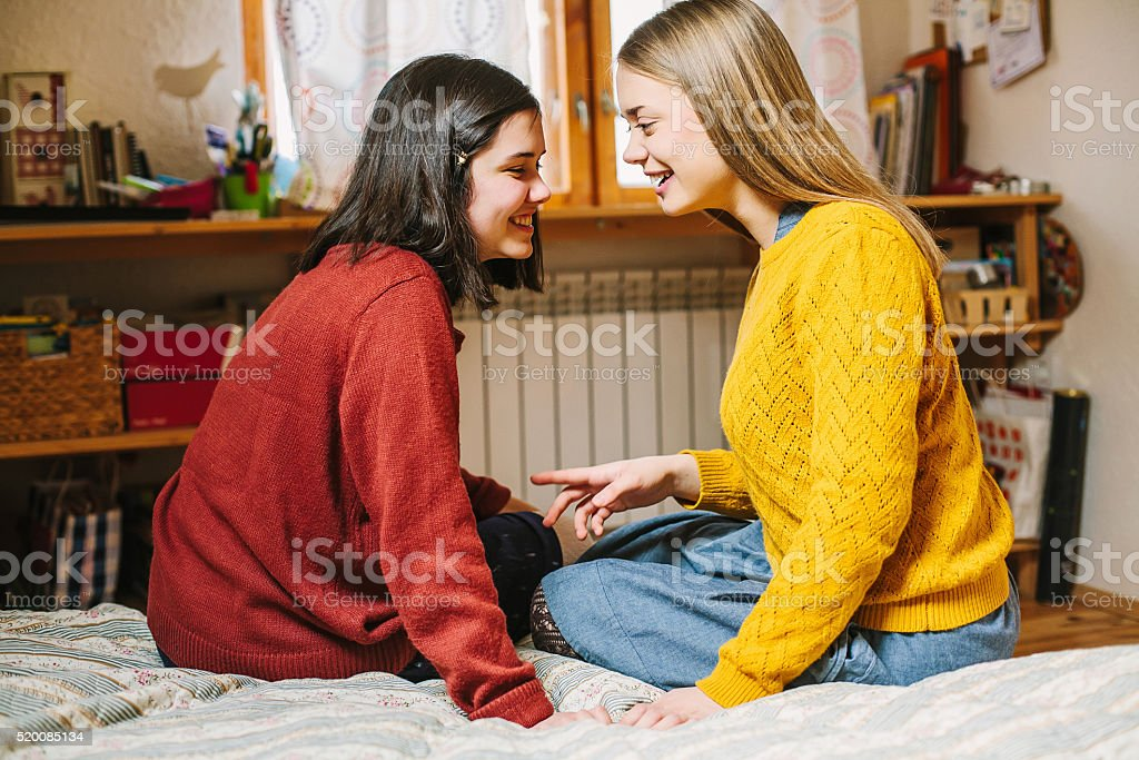 Two girls sitting whispering secret to each other. Shallow focus. stock photo