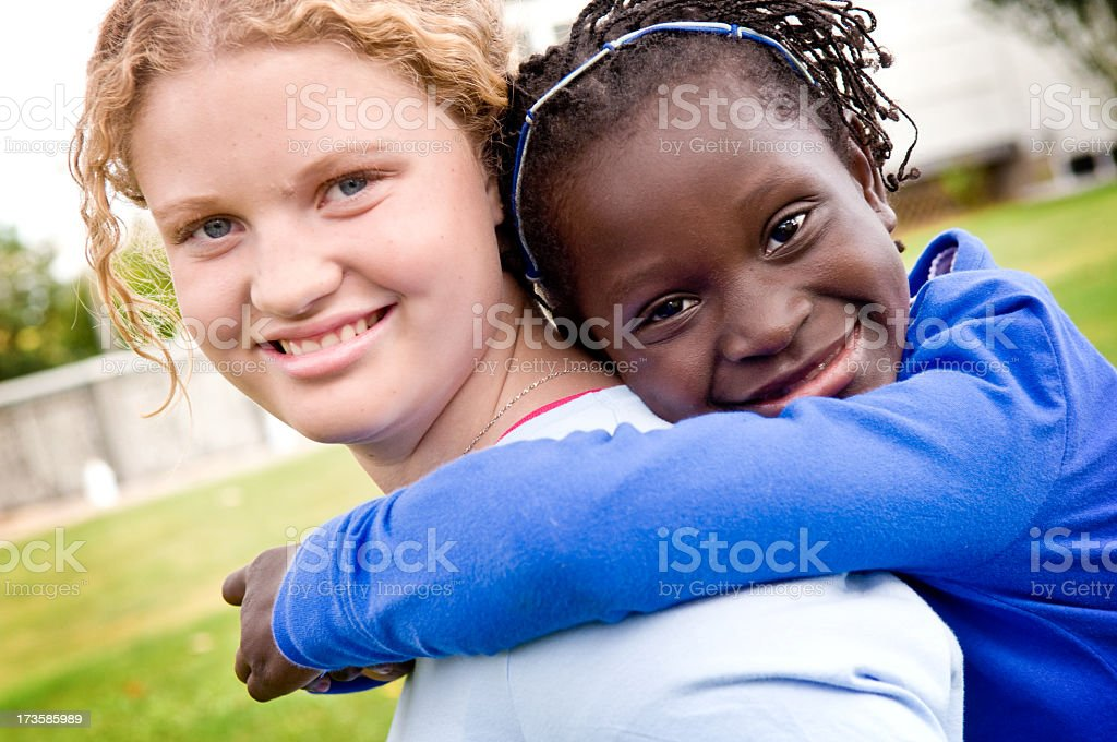 Two Girls Smiling and Hugging Outside royalty-free stock photo