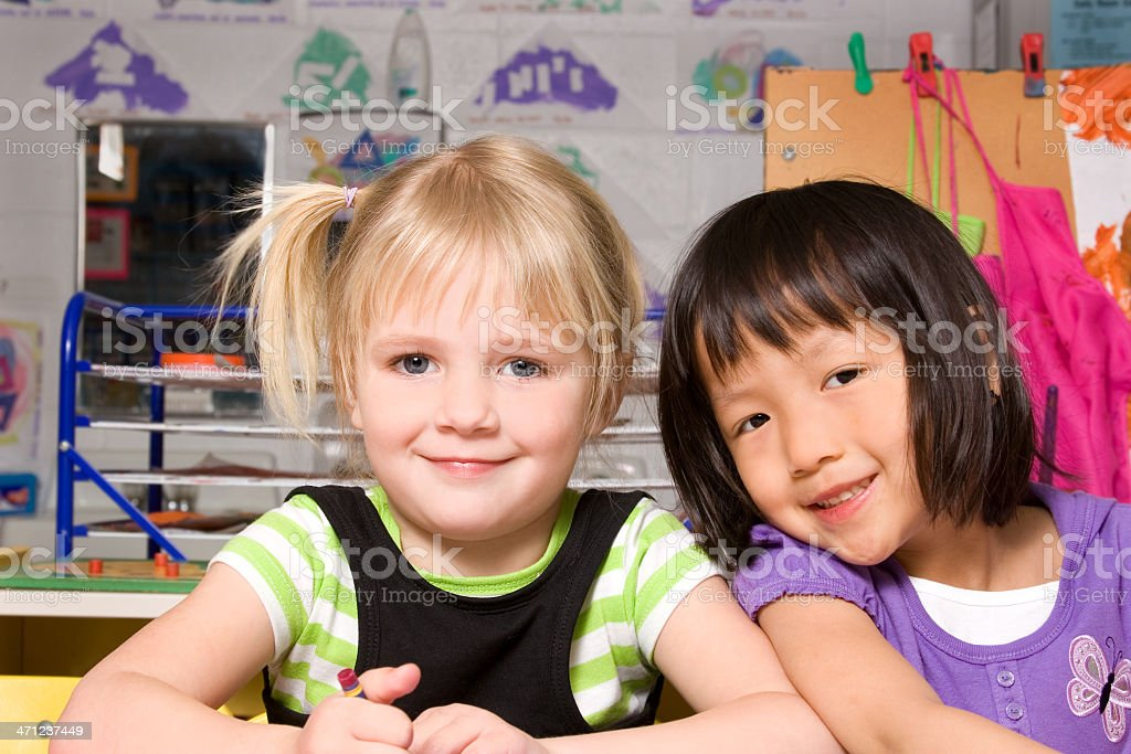 Two girls smiling together in preschool royalty-free stock photo