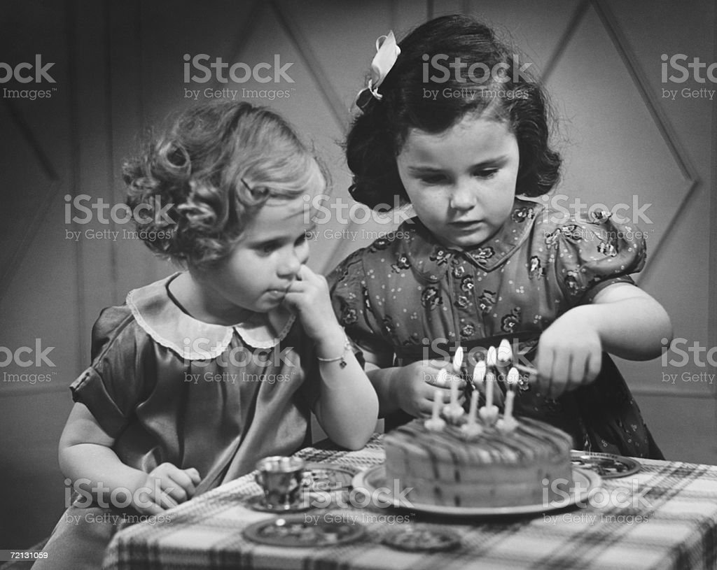 Two girls (4-5) standing at table with birthday cake (B&W) royalty-free stock photo