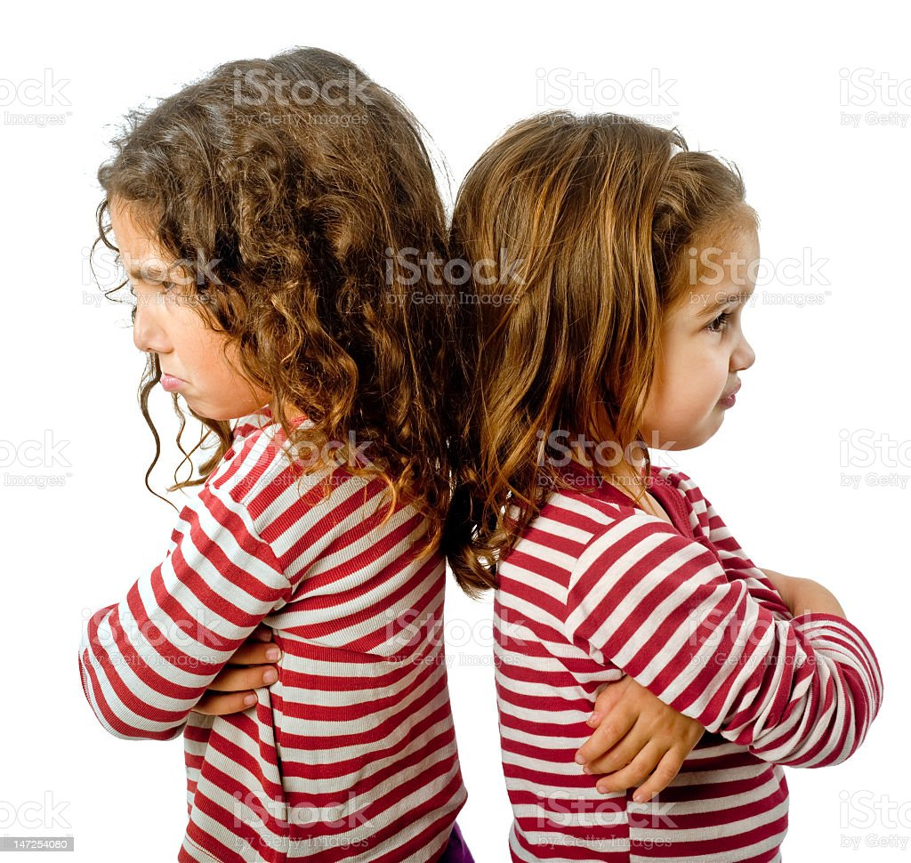 Two girls standing back to back and frowning royalty-free stock photo
