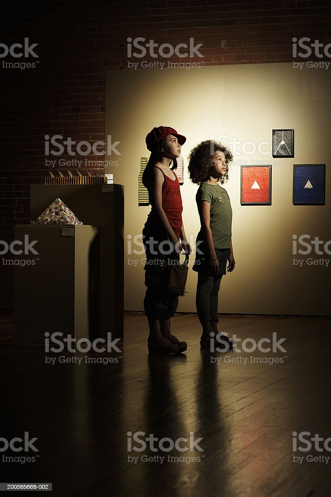 Two girls (10-11) standing in domestic room, side view royalty-free stock photo