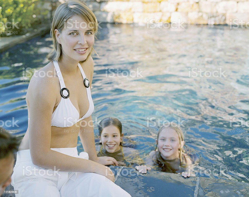 Two girls swimming outdoors with mother royalty-free stock photo