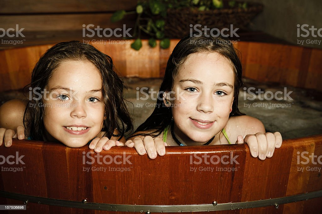 Two girls taking a bath stock photo