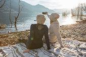 Two girls taking selfie portrait by the lake
