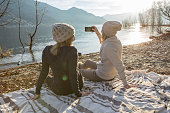 Two girls taking selfie portrait by the lake