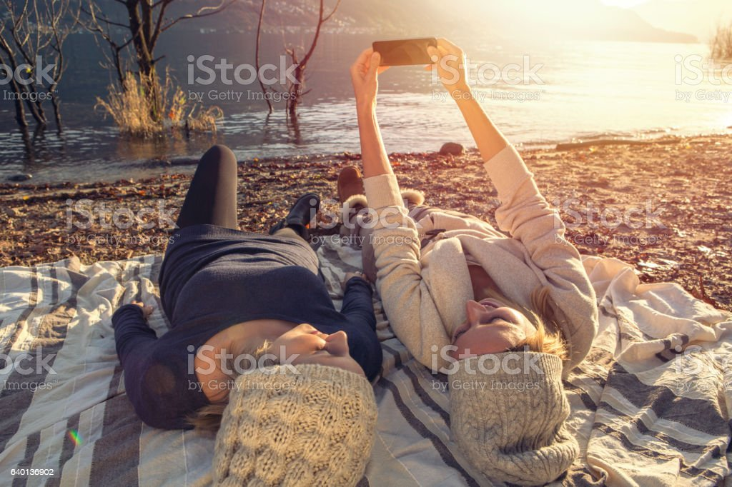 Two girls taking selfie portrait by the lake stock photo