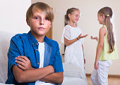 Two girls talking and sulky boy sitting separately at home