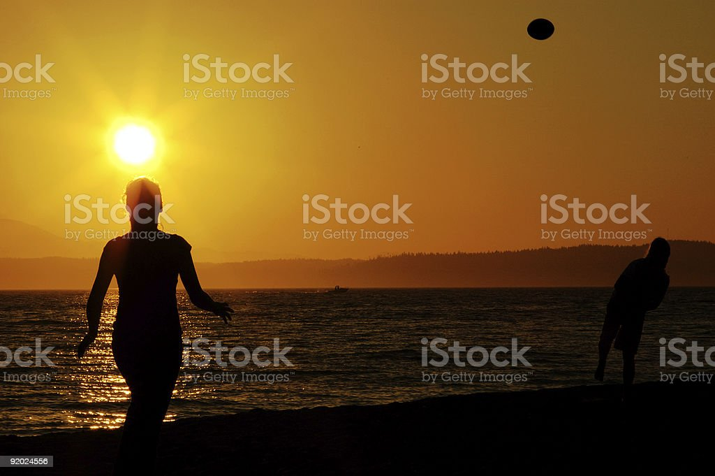 Two Girls Throwing Football on Beach royalty-free stock photo