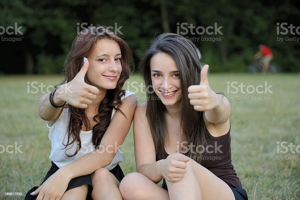 Two girls thumbs up in park royalty-free stock photo