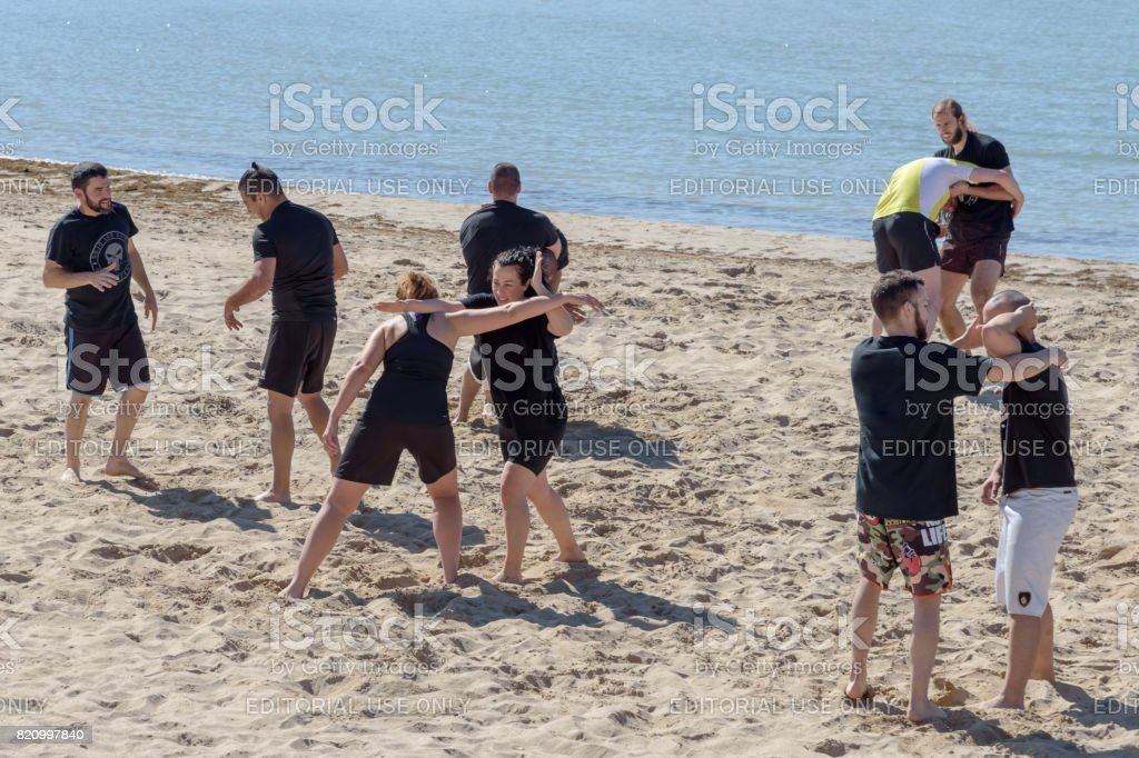 Two girls train are engaged in wrestling on the seashore stock photo