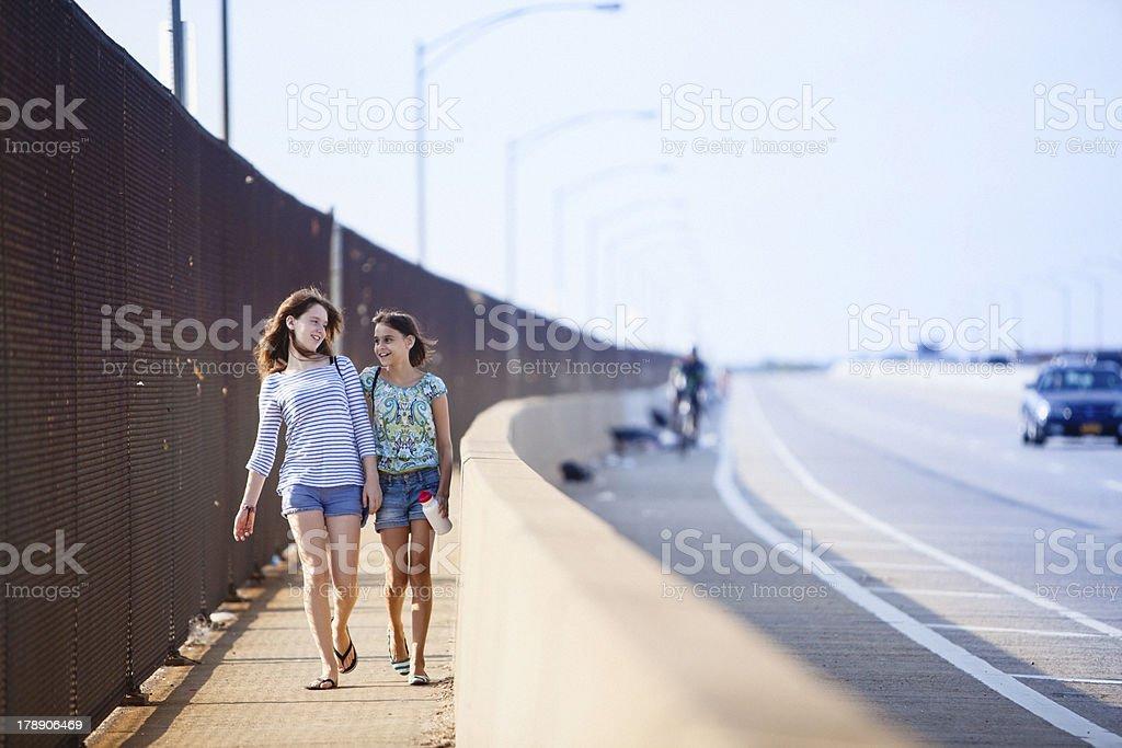 Two Girls Walking Across Bridge in Queens, New York stock photo