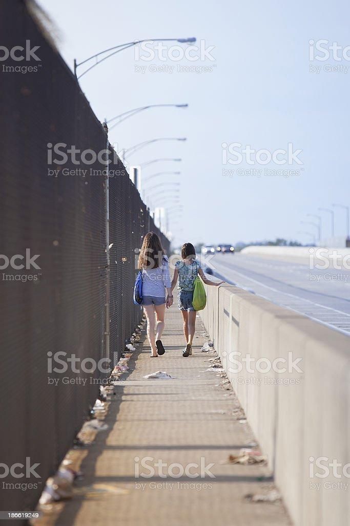 Two girls walking over a bridge  in the industrial zone royalty-free stock photo
