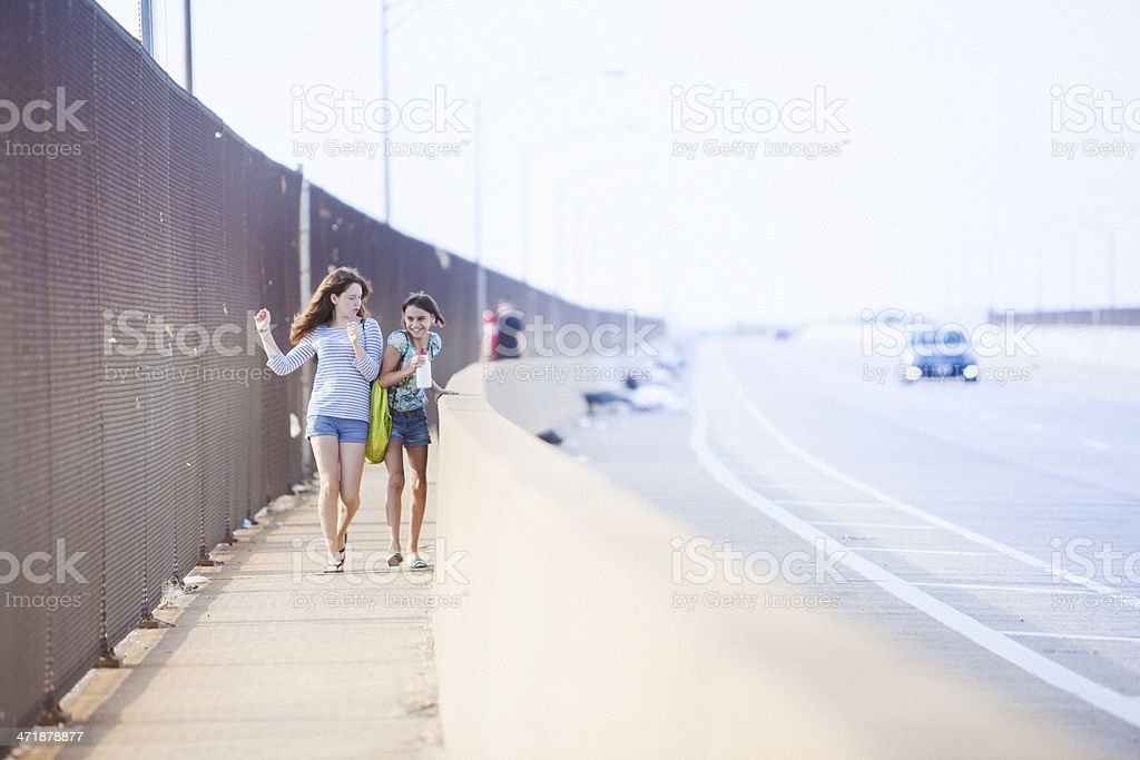 Two girls walking over a bridge  in the industrial zone stock photo