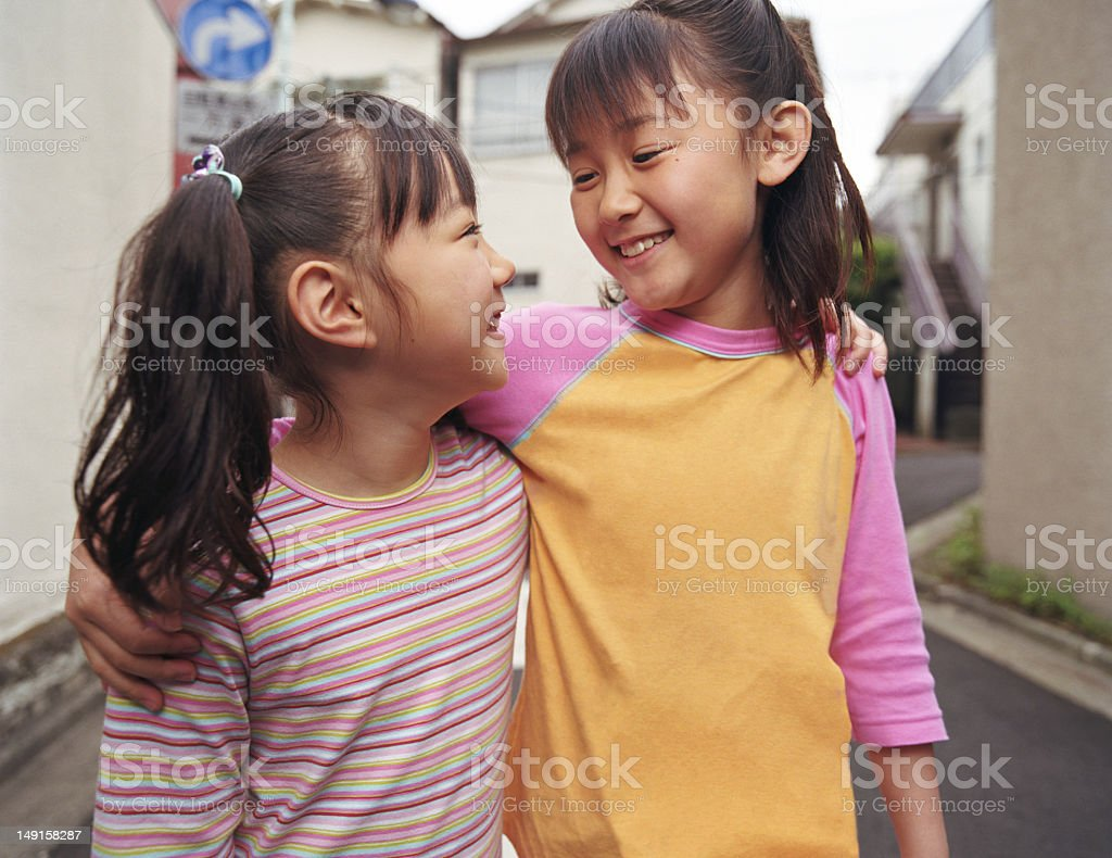 Two girls (6-9) walking with arms around one another, smiling royalty-free stock photo