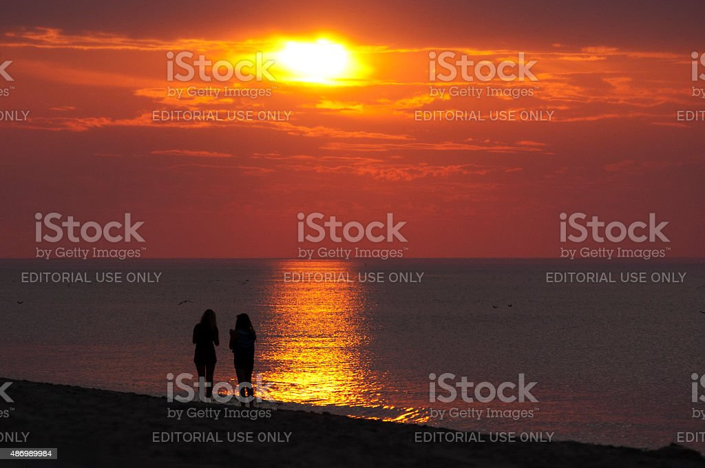 Two girls watching a beautiful sunset at dutch Northsea beach stock photo