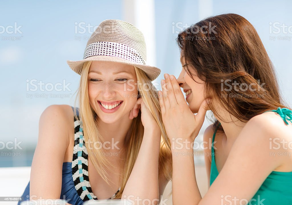 Two girls whispering in a cafe and smiling stock photo