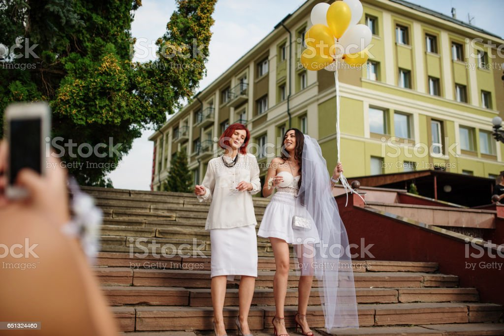 Two girls with balloons at hand on hen party. Making photo by phone. stock photo