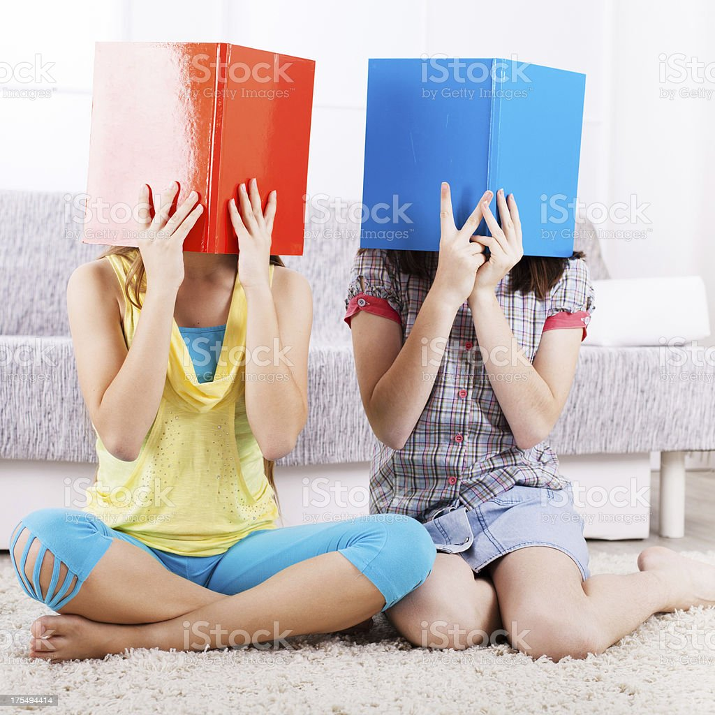 Two girls with books, covering their faces royalty-free stock photo