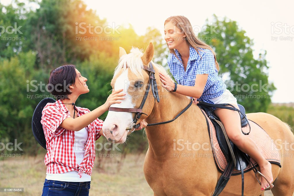 Two girls with horse in nature stock photo