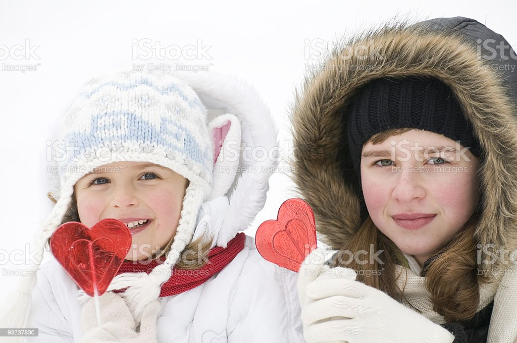 Two girls with lollipops stock photo
