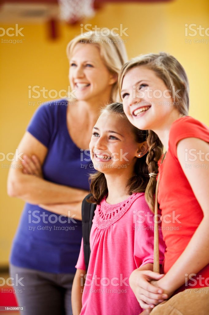 Two girls with mother in background stock photo