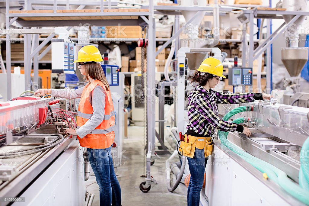 Two girls working in a factory stock photo