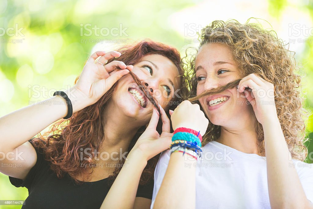 Two girs making moustache with their hair. stock photo