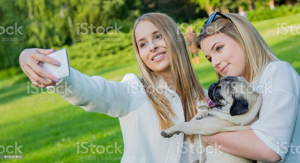 Two girs with a pug taking a selfie stock photo
