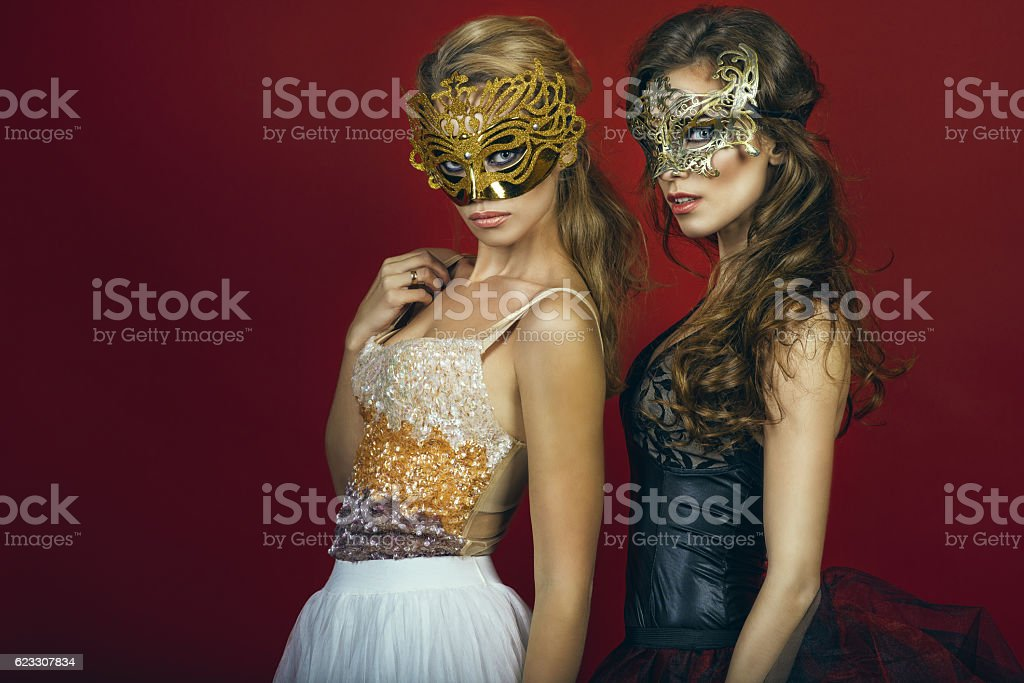 Two glam women in masks on red background stock photo