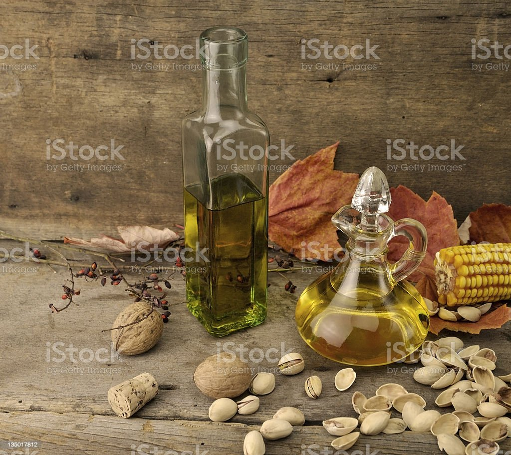 Two glass bottles of olive oil with nuts around them stock photo