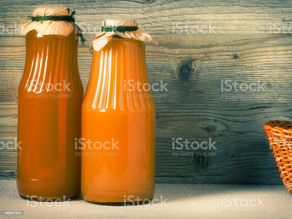 Two glass bottles with juice stock photo