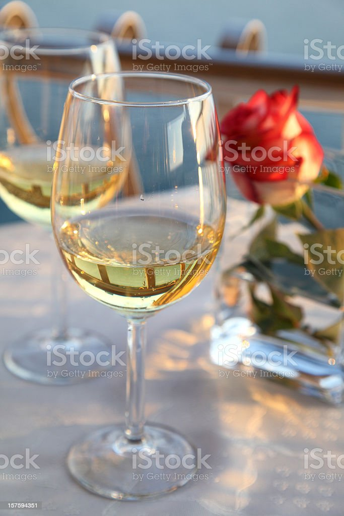 Two glass of wine and red rose on the table royalty-free stock photo