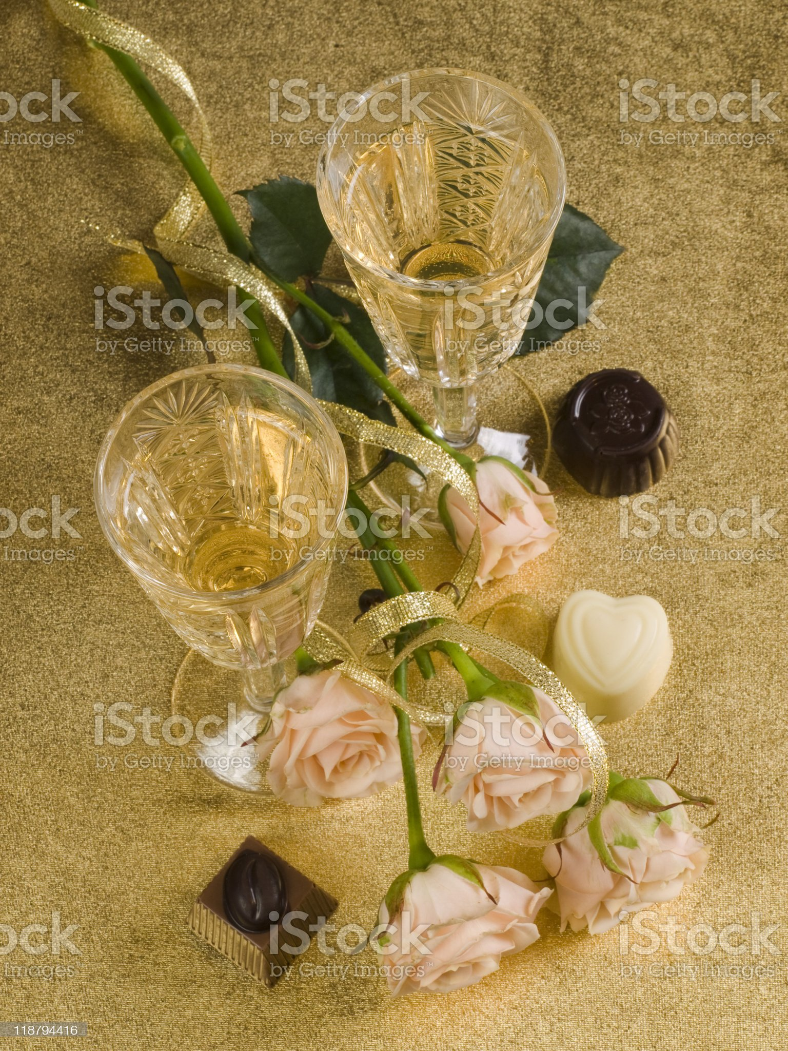 two glass with wine and roses on a gold  background royalty-free stock photo