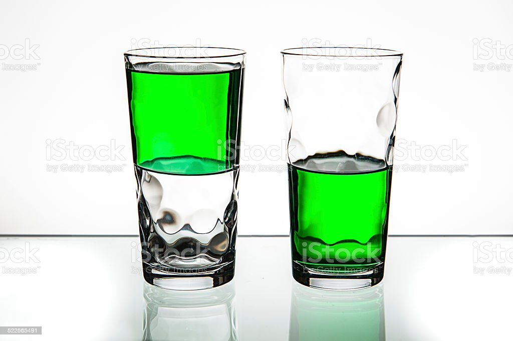 Two glasses, both half-full of green liquid. stock photo