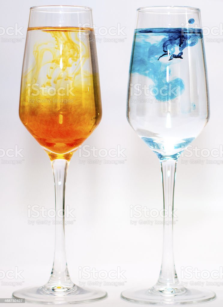 Two glasses filled with water and food colourings stock photo