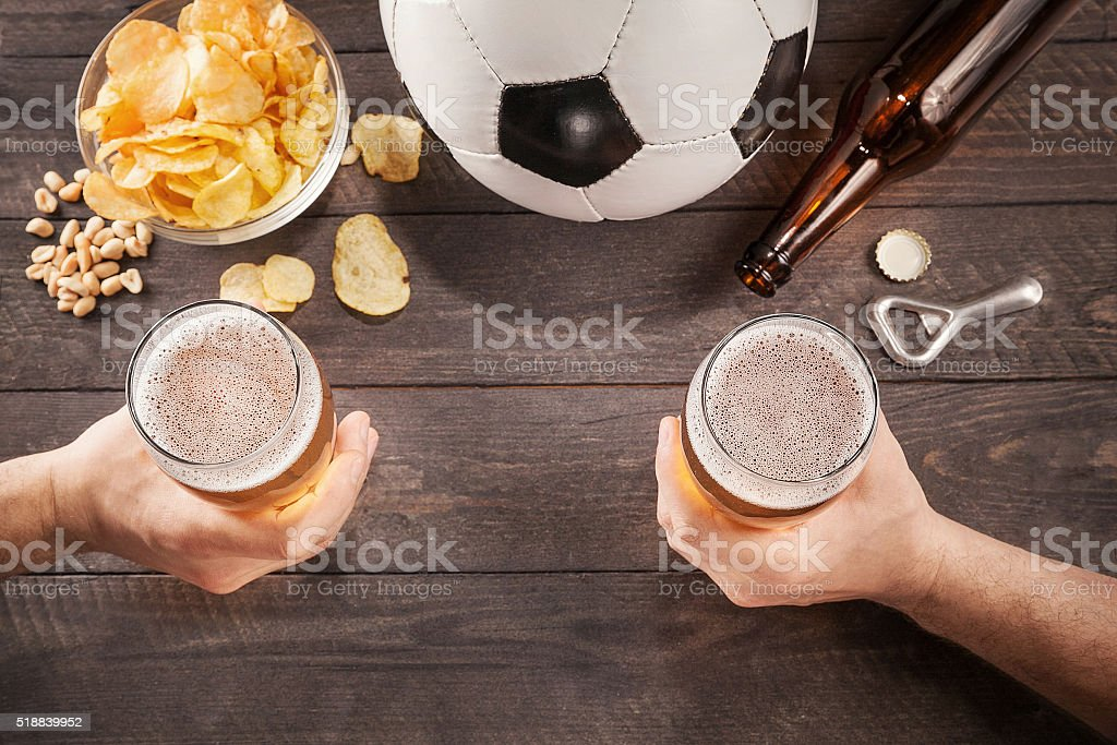 two glasses of beer in men's hands. Chin-chin stock photo
