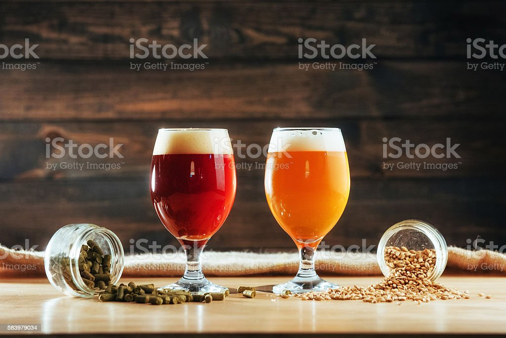 Two glasses of beer on a wooden table grains stock photo