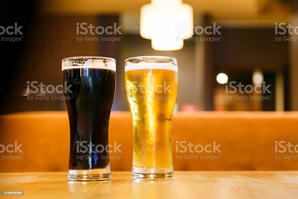 Two glasses of beer over a dark background stock photo