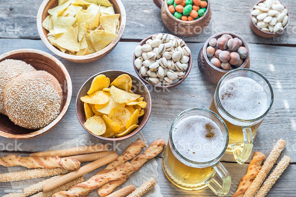 Two glasses of beer with appetizers stock photo
