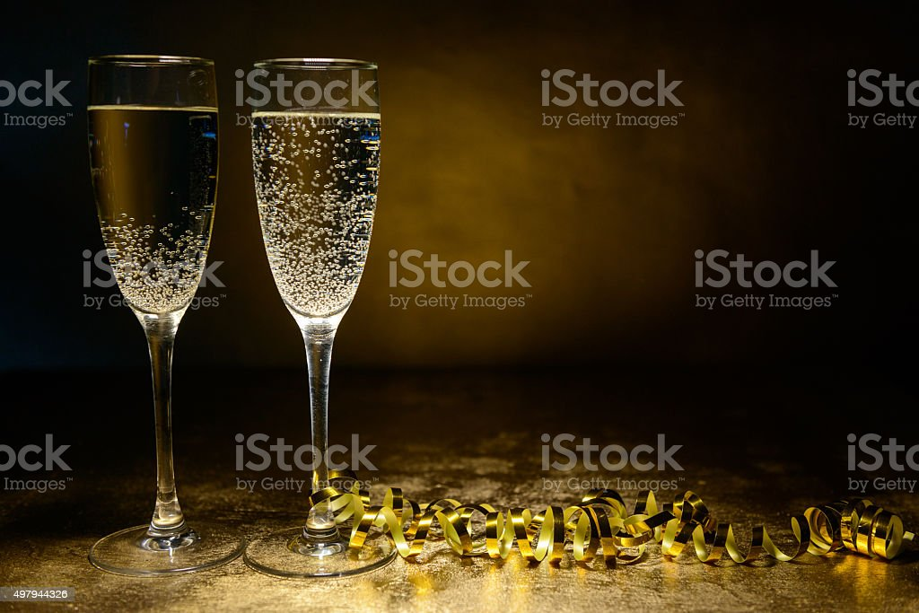 two glasses of champagne on a gold background stock photo