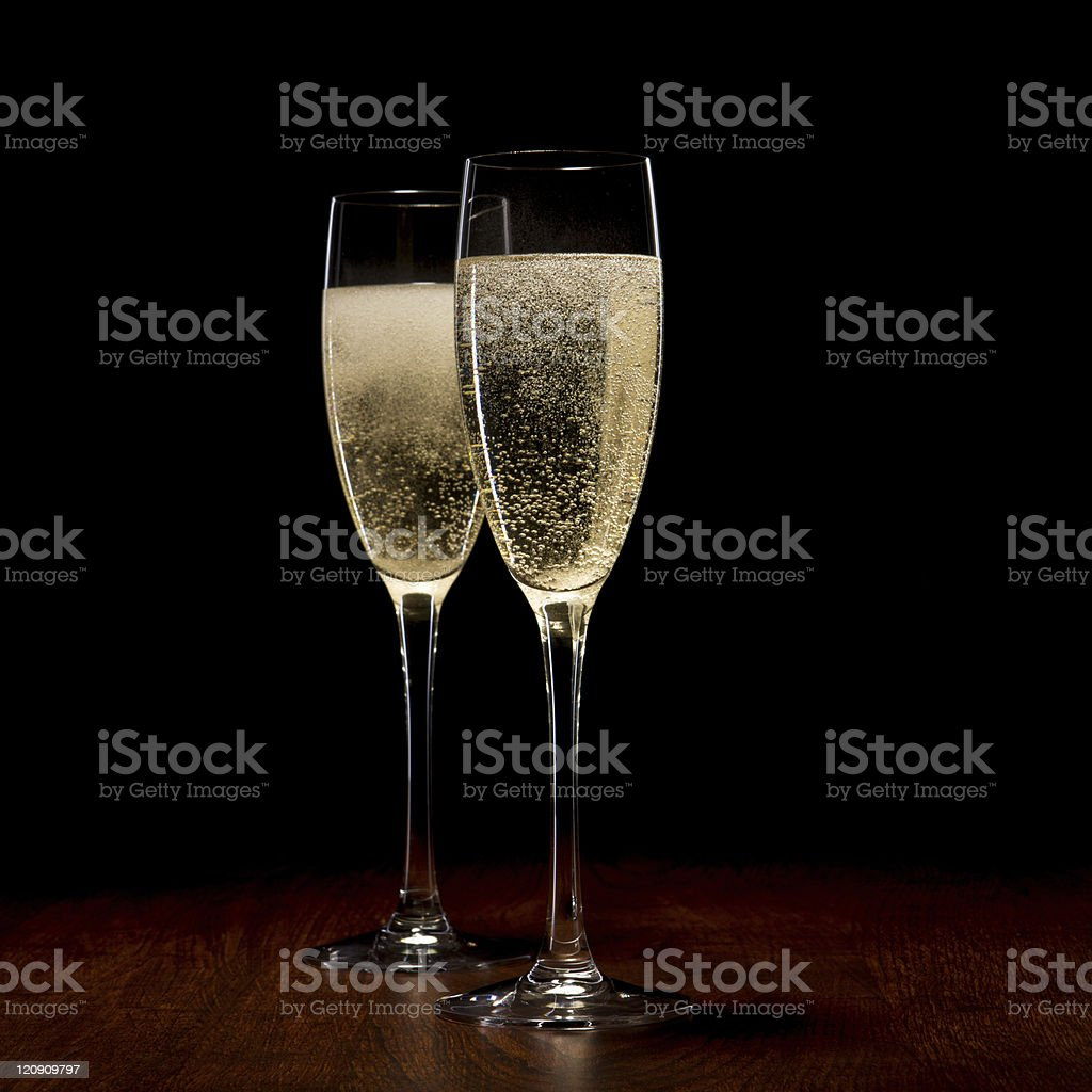 Two glasses of champagne on a wooden table in the dark royalty-free stock photo
