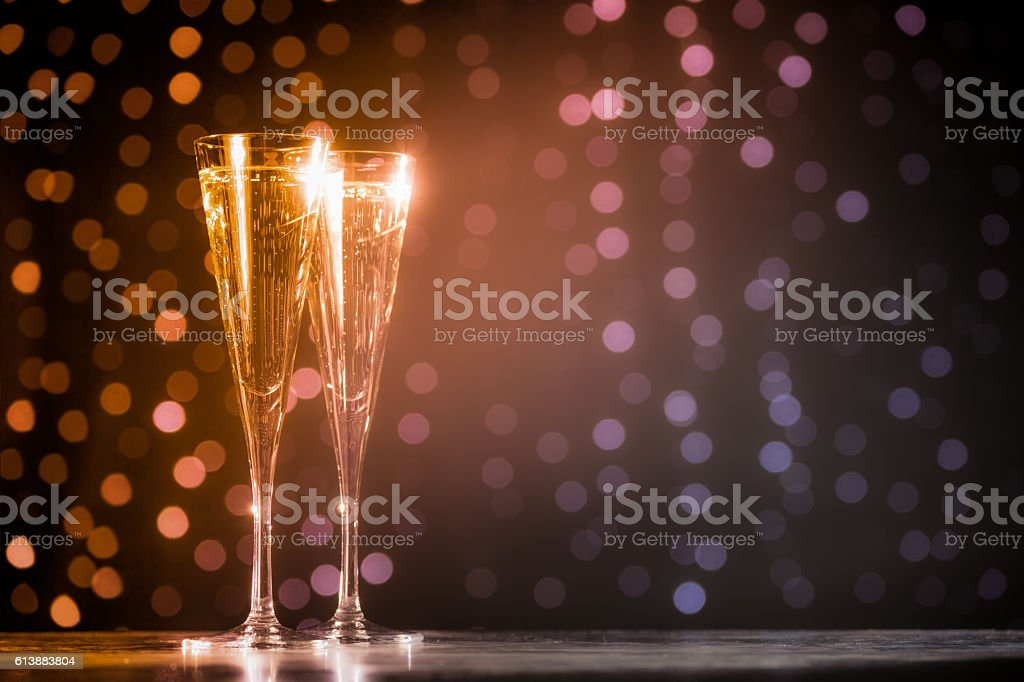 Two glasses of champagne on dark bokeh background stock photo