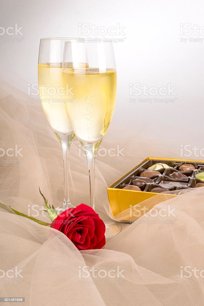 Two Glasses of Champagne, Red Rose and Gourmet Chocolates stock photo