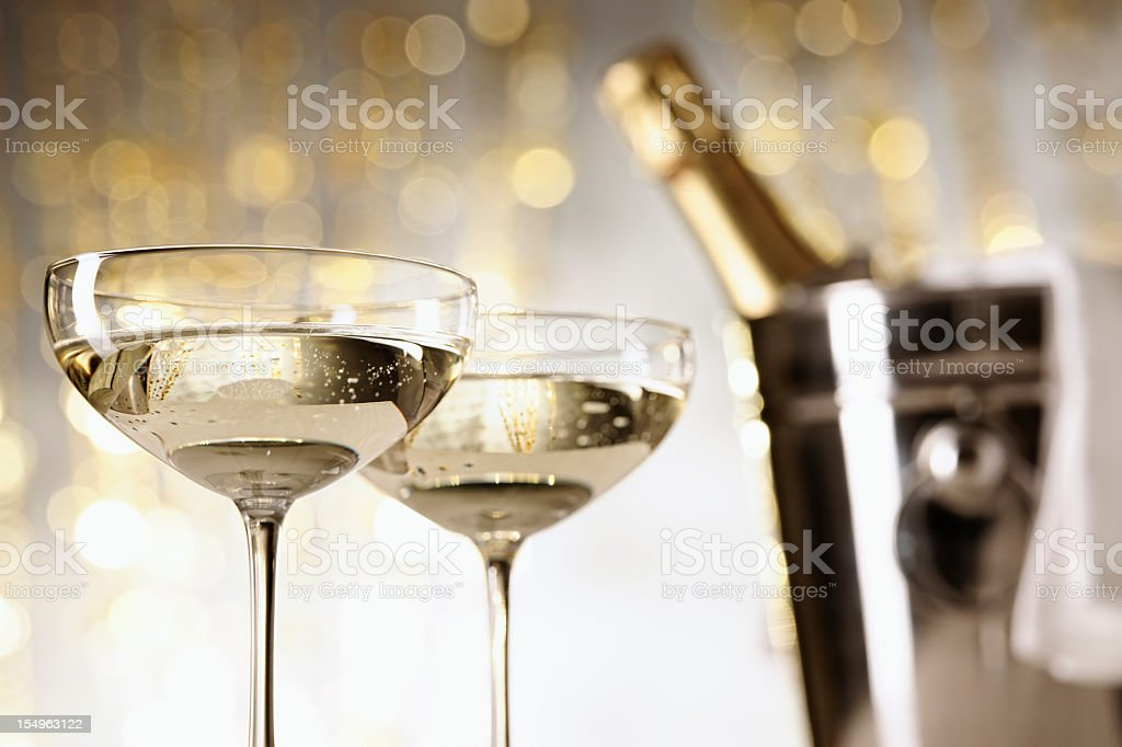 Two glasses of champagne with a blurry bucket with bottle stock photo