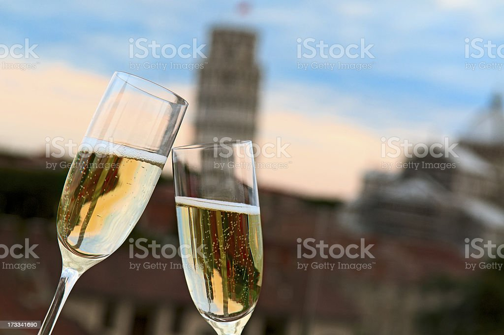 Two glasses of champagne with blurry Pisa tower in the back stock photo