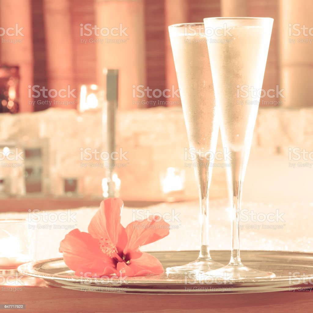 Two glasses of champagne with candle and red flower near jacuzzi. Valentines background. Romance concept stock photo