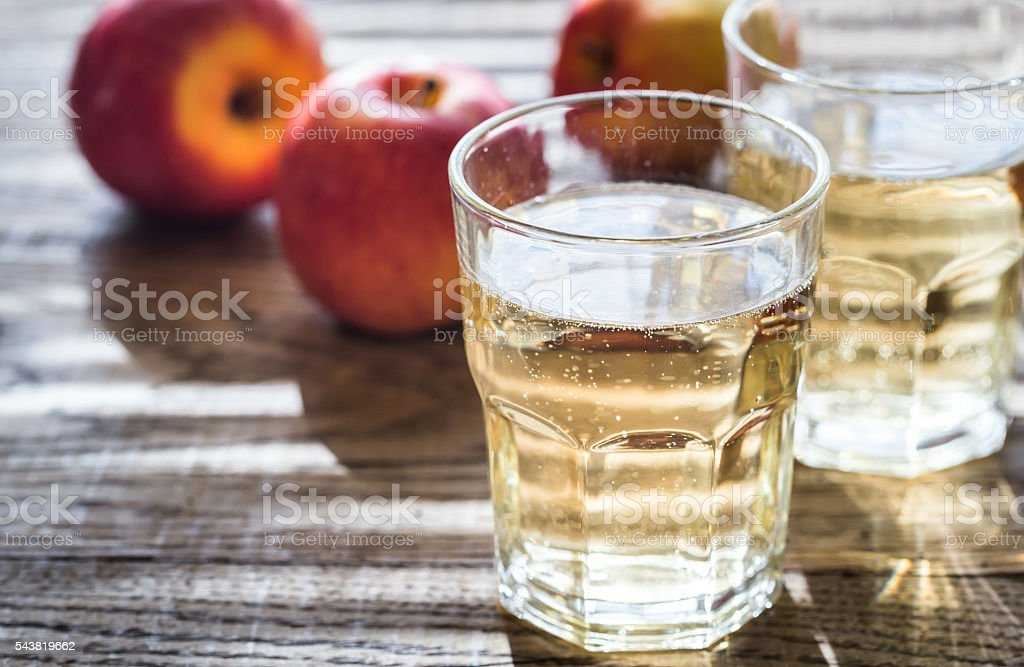 Two glasses of cider on the wooden background stock photo