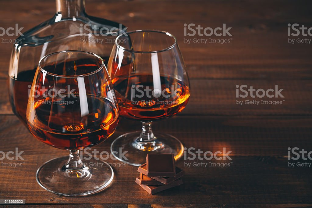 Two glasses of cognac and bottle on the wooden table. stock photo